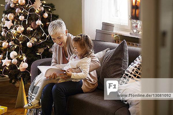 Großmutter hilft Mädchen beim Lesen von Büchern  während sie zu Hause auf dem Sofa sitzt
