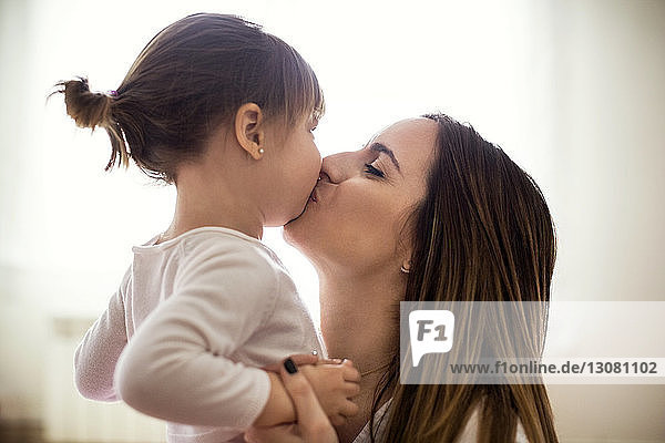 Seitenansicht einer liebenden Mutter  die ihre Tochter zu Hause küsst
