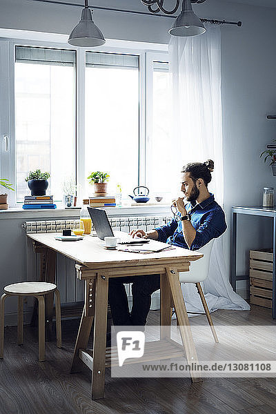 Man using laptop computer while sitting by window at home