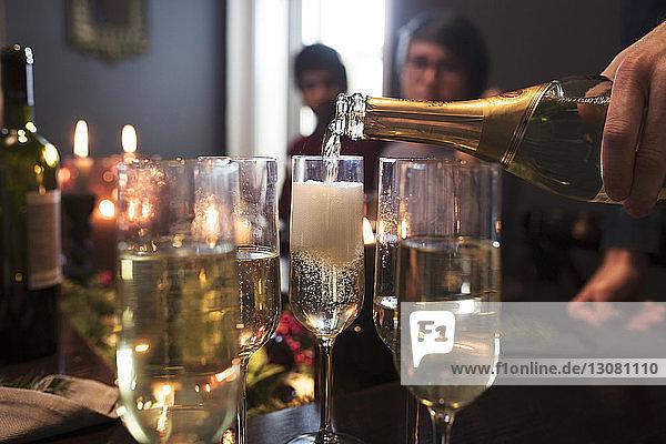 Nahaufnahme eines Mannes  der während der Weihnachtsfeier Champagner in Gläser gießt