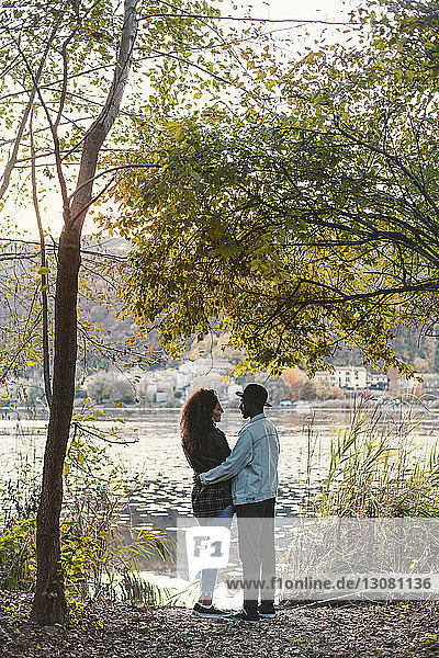 Side view of romantic couple standing at lakeshore