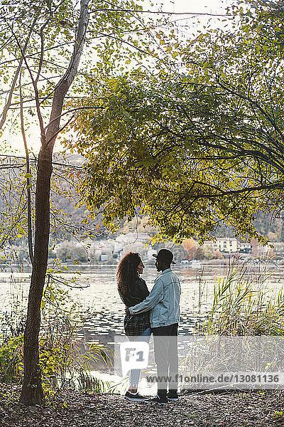 Seitenansicht eines am Seeufer stehenden romantischen Paares
