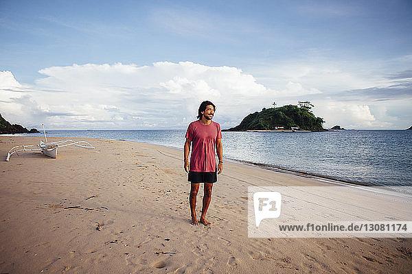 Mann schaut weg und steht am Strand vor bewölktem Himmel