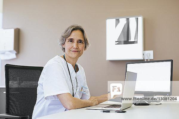 Porträt eines leitenden Arztes  der im Krankenhaus an einem Laptop-Computer arbeitet