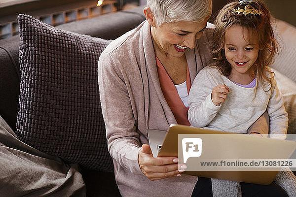 Glückliche Großmutter und Enkelin mit Laptop auf dem Sofa