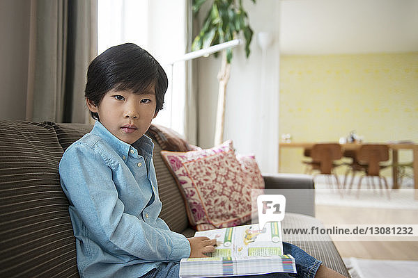 Portrait of boy with book sitting on sofa at home