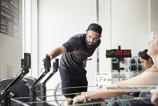Instructor checking rowing machine while women exercising in crossfit gym