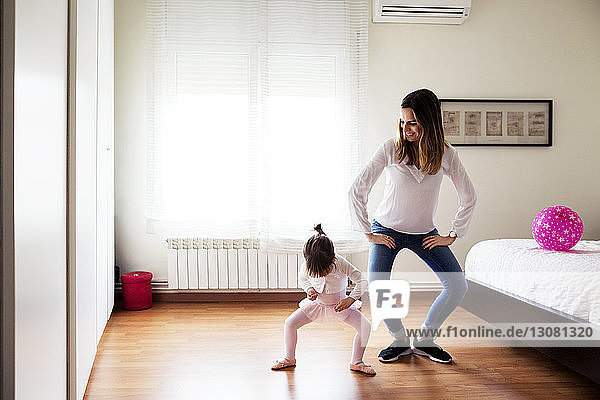 Smiling mother imitating girl performing ballet dance in bedroom