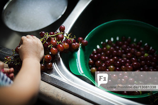 Cropped image of girl with red grapes in kitchen