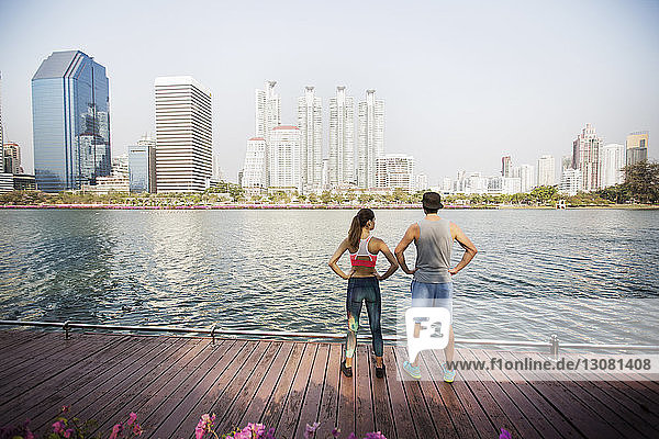 Rear view of couple standing with hands on hip at wooden walkway by river