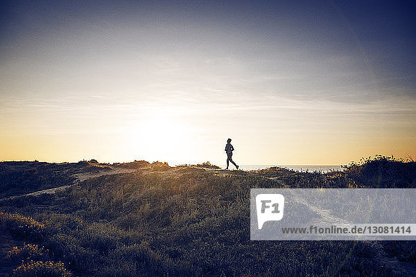 Distant view of woman jogging on field against sky
