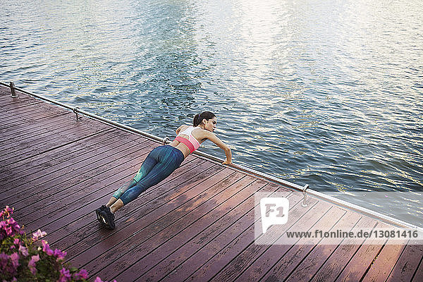 High angle view of woman performing pushups at wooden walkway by river