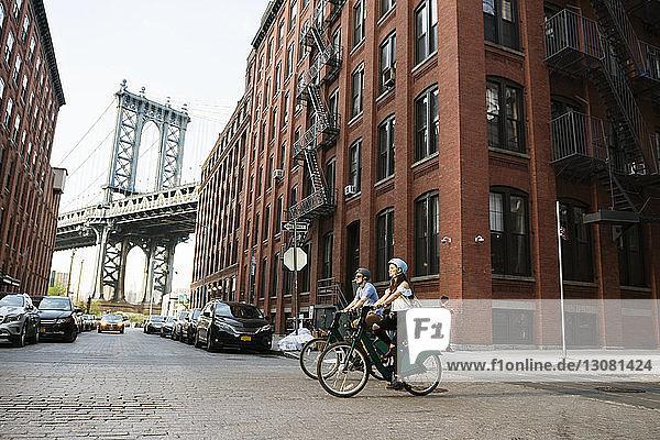 Ein Paar radelt auf der Straße an Gebäuden in der Stadt vorbei gegen die Manhattan-Brücke