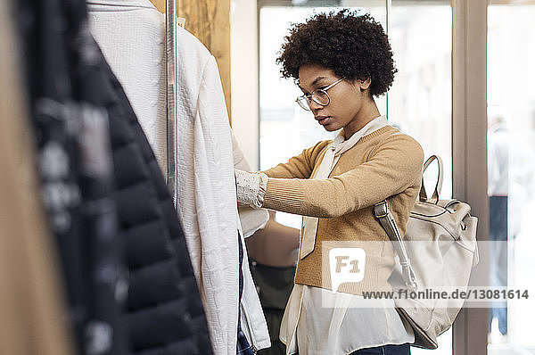 Concentrated woman searching for tops at clothes rack in shop