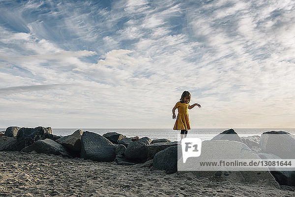 Playful girl walking on rocks at beach against cloudy sky during sunset
