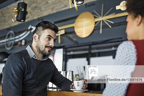 Junger Geschäftsmann schaut Frau im Cafe an
