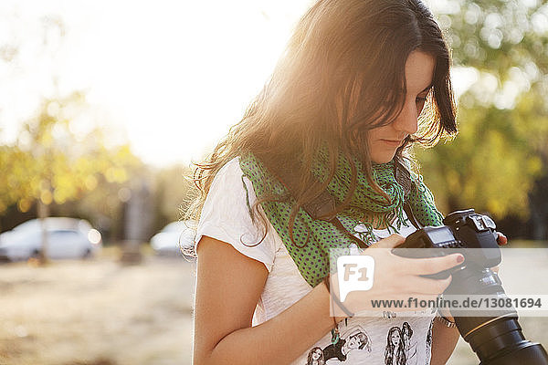 Junge Frau hält Kamera im Feld gegen klaren Himmel