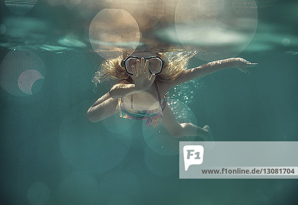 Carefree girl wearing goggles while swimming underwater in pool