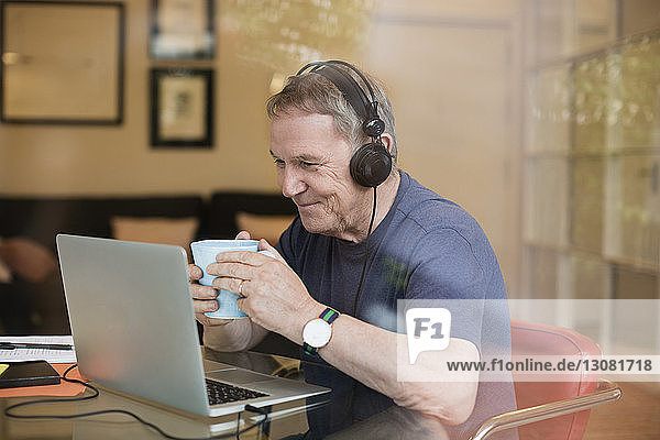 Happy senior man having coffee while listening music through laptop at home