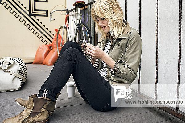 Junge Frau benutzt ein Smartphone  während sie auf einem Fußweg im Freien sitzt
