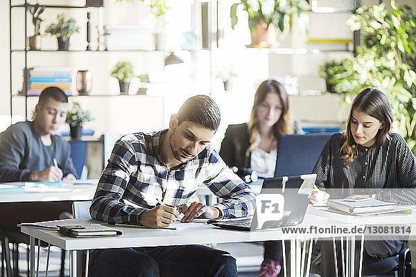 Schüler  die während des Unterrichts im Klassenzimmer an Tischen sitzen