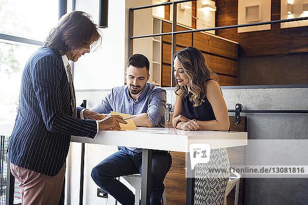 Geschäftsmann diskutiert mit Kollegen am Schreibtisch im Büro