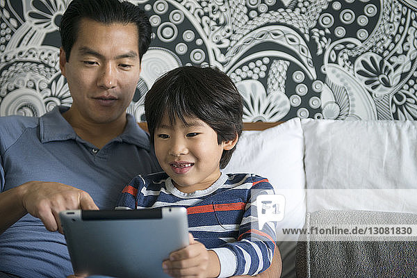 Close-up of father and son using digital tablet on bed