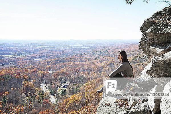 Seitenansicht einer Frau  die auf einem Felsen gegen den Himmel sitzt