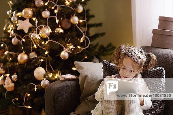 Mädchen benutzt einen Tablet-Computer  während sie zu Weihnachten auf dem Sofa sitzt