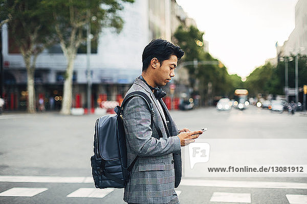 Side view of businessman with backpack using smart phone while standing on street