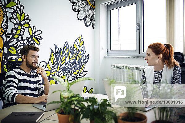 Männliche und weibliche Kollegen diskutieren im kreativen Büro