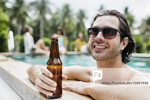 Nachdenklicher Mann hält Bierflasche im Schwimmbad