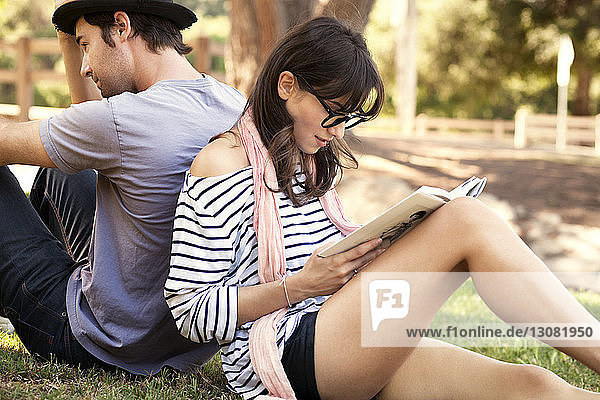 Woman reading book while sitting with man at park