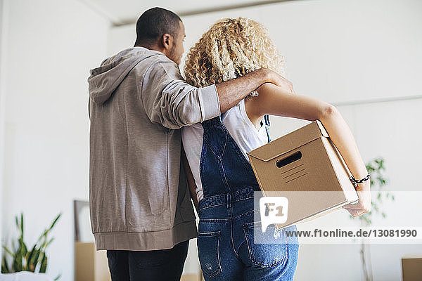 Rear view of woman carrying box standing with husband at new house