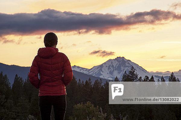 Rückansicht einer Frau  die im Shevlin Park gegen Berg und Himmel steht
