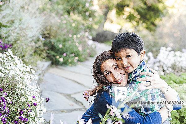 Hochwinkelporträt von glücklicher Mutter und Sohn im Park