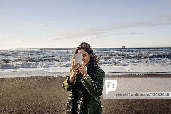 Schöne Frau fotografiert durch Smartphone-Strand