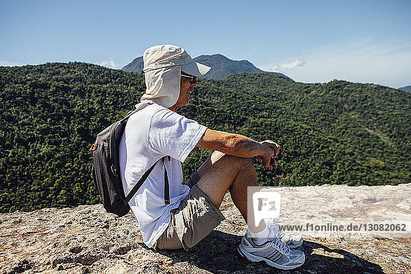 Side view of male hiker sitting on mountain against blue sky during sunny day