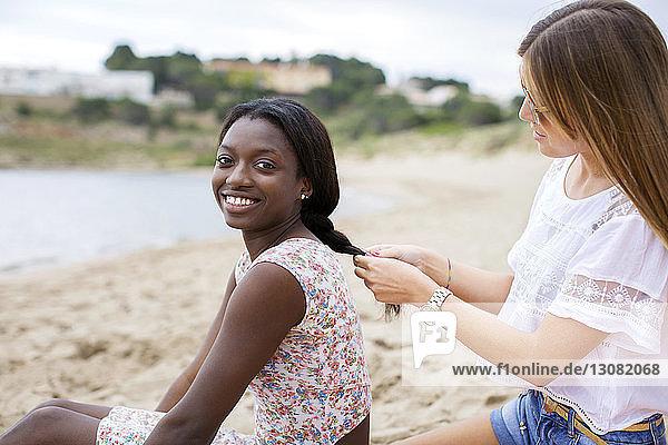 Seitenansicht einer Frau  die am Strand einem Freund die Haare flechtet