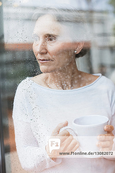 Thoughtful mature woman looking through window while holding coffee mug at home