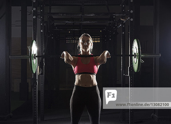 Portrait of determined female athlete lifting barbell in gym