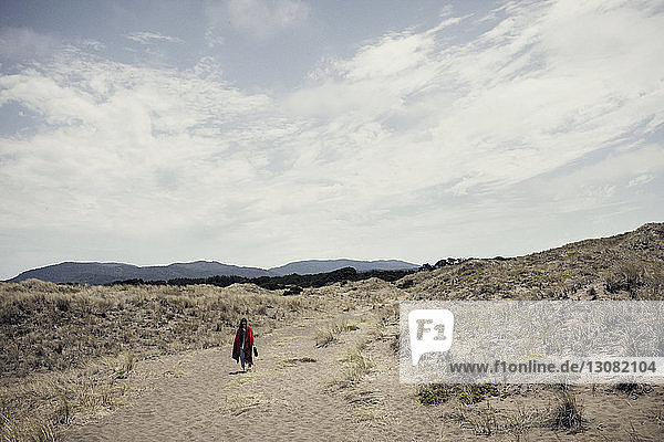 Frau mit Decke geht auf Feld gegen Himmel