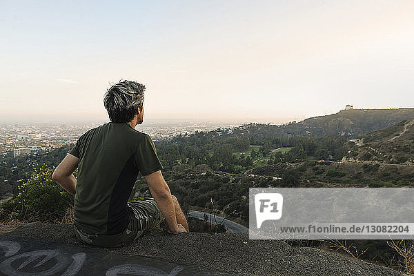 Young man looking at view while sitting on rock against sky during sunset
