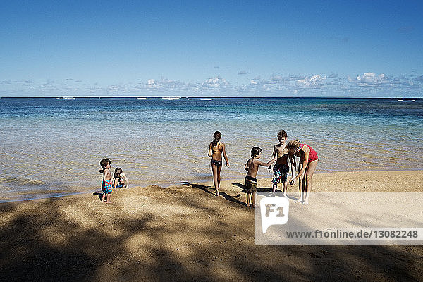 Family with five children on beach by sea