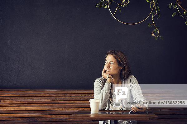 Nachdenkliche Frau schaut weg  während sie an einem Café-Tisch sitzt