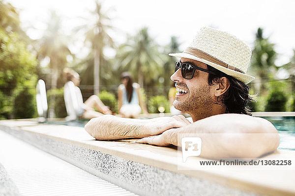 Nachdenklicher Mann entspannt sich im Schwimmbad eines Touristenortes