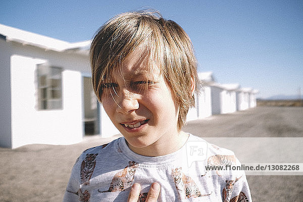 Close-up portrait of boy against houses during sunny day