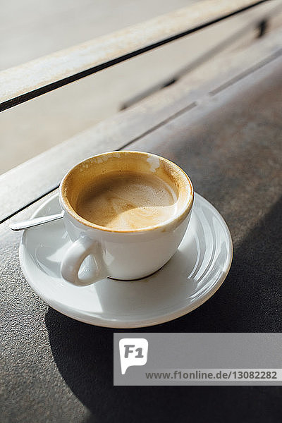Close-up of coffee on table by window in cafe