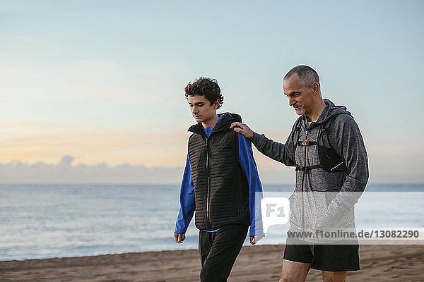 Vater und Sohn gehen bei Sonnenaufgang am Strand gegen den Himmel