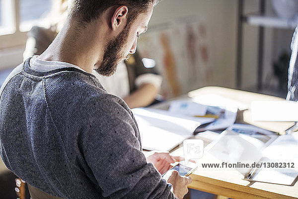 Mann benutzt ein Smartphone  während er im Klassenzimmer am Tisch sitzt